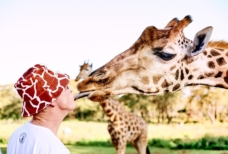 The-Safari-Collection-Man-in-Giraffe-Hat-Kissing-Giraffe-at-Giraffe-Manor- be107416caf